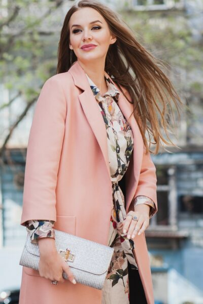 attractive stylish smiling woman walking city street in pink coat spring fashion trend holding purse